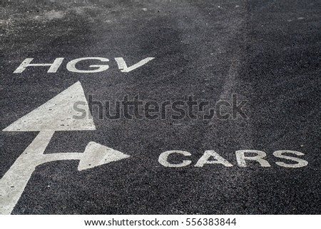 White painted arrow on the tarmac directs cars and trucks to different areas #556383844