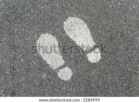 White painted footprints on asphalt road.