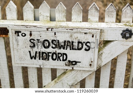 White painted sign to footpath to ancient church of St Oswald in Widford Oxford