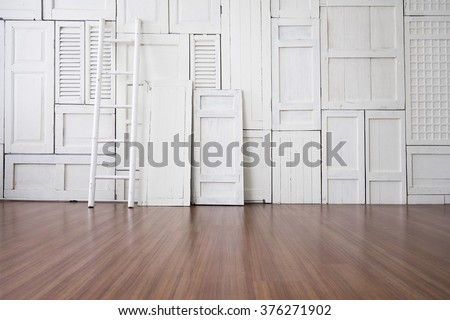 White painted window hinge on wall with white ladder on wooden floor