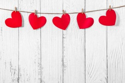 White painted wooden background with a garland of red hearts. Natural rope and clothespins. Concept of recognition of love, romantic relationships, Valentine's day in grunge style. Copy space