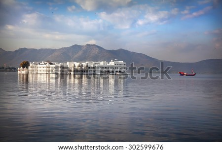 White palace and boat on Lake Pichola at cloudy sky in Udaipur, Rajasthan, India