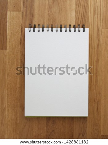 White paper, album, opened sketchbook  on wooden background