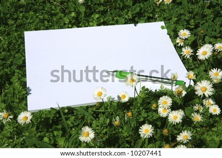 White paper and pen on the grass with space for text - stock photo