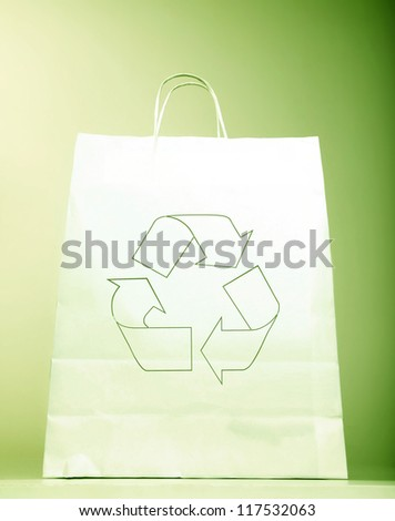 White paper bag with ecology symbol, present with recycle sign isolated on green background, recyclable shopping bag & Eco icon, concept idea to help to save planet  earth from pollution