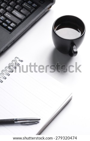White paper blank notebook on the computer white desk. Lap top is black. Black coffee is on desk./White paper notebook on white desk