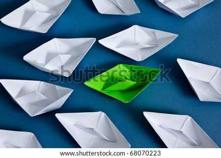 White paper boats and one green boat.
