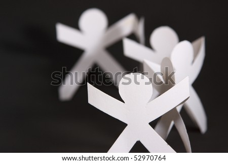 White paper cut into people hold their hands connected on black background