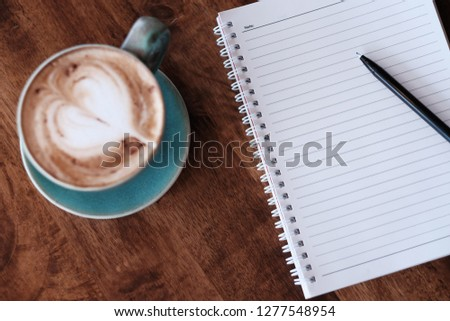 White paper for note on the wooden table with a vintage emerald cup of coffee in working space.