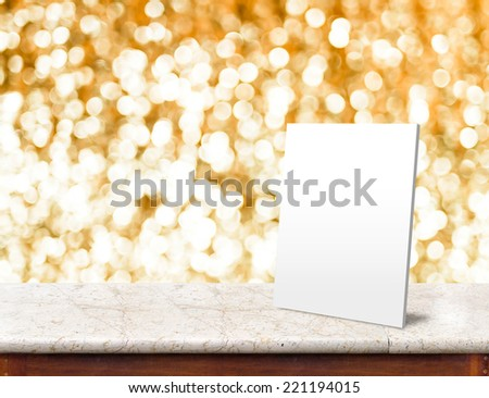 White paper frame at marble Table with bokeh golden sparkling background,Empty room for display your product