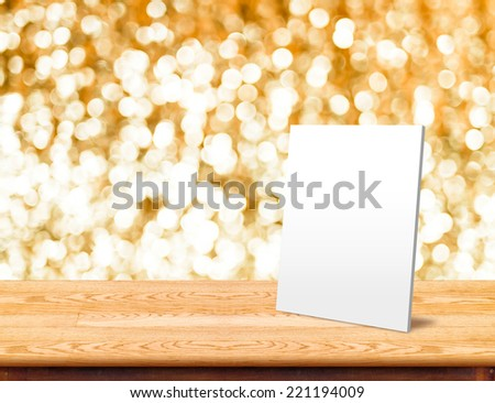 White paper frame at Wood Table with bokeh golden sparkling background,Empty room for display your product