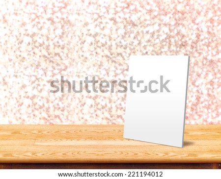 White paper frame at Wood Table with bokeh pink sparkling background,Empty room for display your product