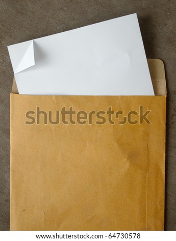 White paper from a brown open envelope on wood table