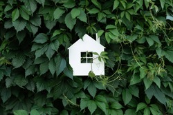 White paper house on a background of green leaves and plants. Eco friendly home concept. Backdrop with copyspace.
