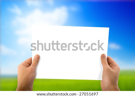 white paper in hand and green field