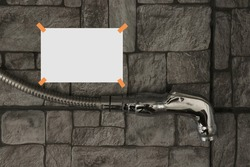 White paper is blank with 4 orange types to the wall, a stanless steel water nozzle on gray-patterned backdrop.