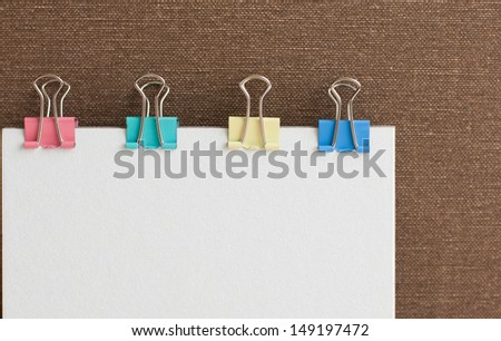 White paper note with  colorful paper clips