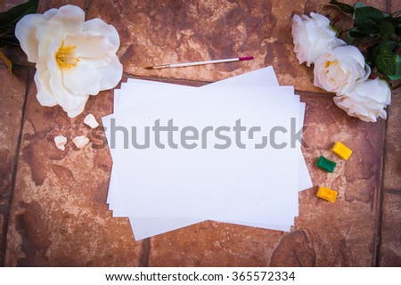 White paper on a stone wall background. Watercolor mock up for presentations. Vintage Desktop workplace designer, artist, painter top view, white flowers roses. Modern trend template for advertising.