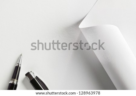 White paper, partially rolled up, and pen