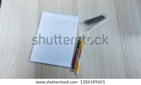 white paper, pens and stapler on wood background.