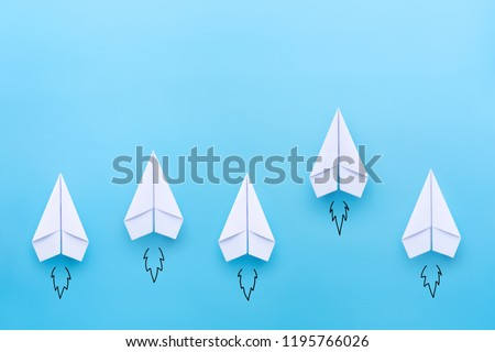 White paper planes on blue background. Business competition concept.