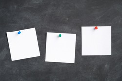 White paper sticky notes with pin clips on black board. Memo sticky notes mockups.