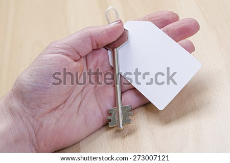 white paper tag attached to the metal silver key in hand