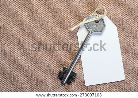 white paper tag attached to the metal silver key on the brown background