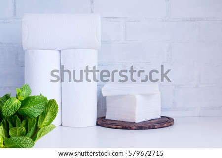 White paper towel rolls and paper napkins, tissue on white board against white brick wall background. #579672715