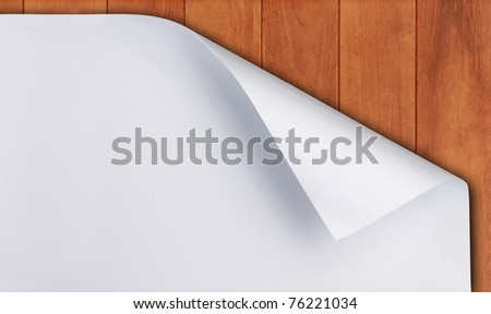 White paper with corner curl over wooden background