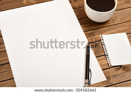 White paper with cup of coffee on wooden table