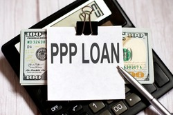 White paper with text PPP Loan with dollars on the calculator with pen