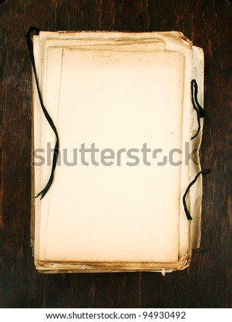 white papers with old book as background vertical