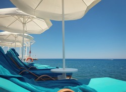 White parasols and sun beds with towels on wooden pier in summer.. Summer vacation during coronavirus pandemic concept. Clear blue sky above the turquoise sea.