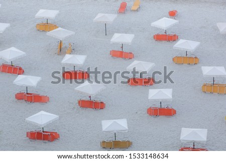 White parasols with yellow and orange beach chairs on a beautiful sandy beach, no people	 #1533148634