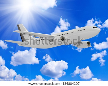White passenger airliner flies under the bright sun in the blue sky above the clouds