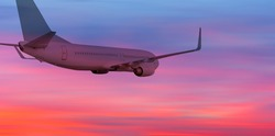 White passenger airplane flying away in to sky high altitude during red sunset time