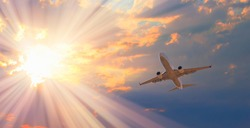 White passenger airplane flying away in to sky high altitude during sunset time