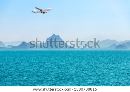 white passenger airplane landing above group of small island and many layers mountain in tropical turquoise sea travel destinations concept.