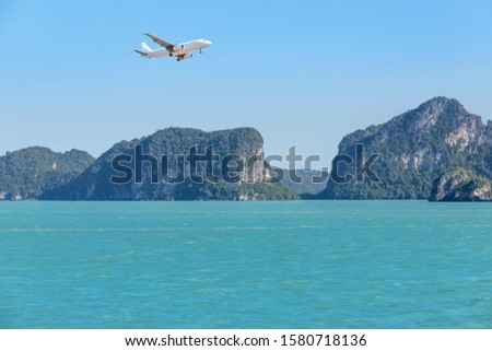 white passenger airplane landing above group of small island in tropical turquoise sea travel destinations concept.