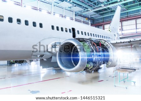 White passenger airplane under maintenance in the hangar. Repair of aircraft engine on the wing and checking mechanical systems for flight operations