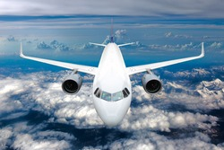 White passenger jet plane in the blue sky.  Aircraft flying high above the mountains. Airplane front view.
