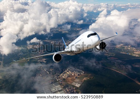 Photo of  White passenger plane climbs through the clouds. Aircraft is flying high above the city.