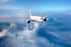 White passenger plane flies over the clouds. Front view of aircraft. Travel and transportation concept.