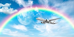 White passenger plane flying in the sky with full moon and rainbow.