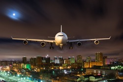 White passenger plane in flight during the night. Aircraft flying in moonlight over the night city. Airplane front view.