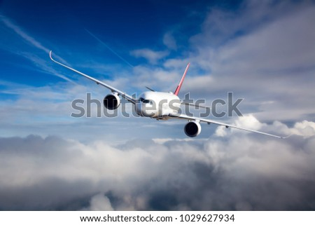 White passenger plane in flight. The plane flies against a background of a cloudy sky. Aircraft right inclination / front view.