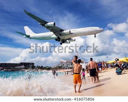 Shutterstock White passenger wide-body plane in the blue cloudy sky. Aircraft is flying low over the beach, sea and swimming tourists.