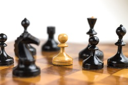 White pawn surrounded by black chess pieces on a chess board