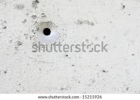 White peeling paint aluminium plate with bullet hole